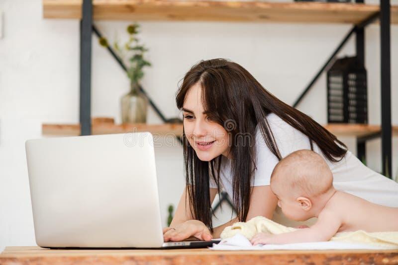 Jeune mère avec le nourrisson et l'ordinateur portable de bébé images libres de droits