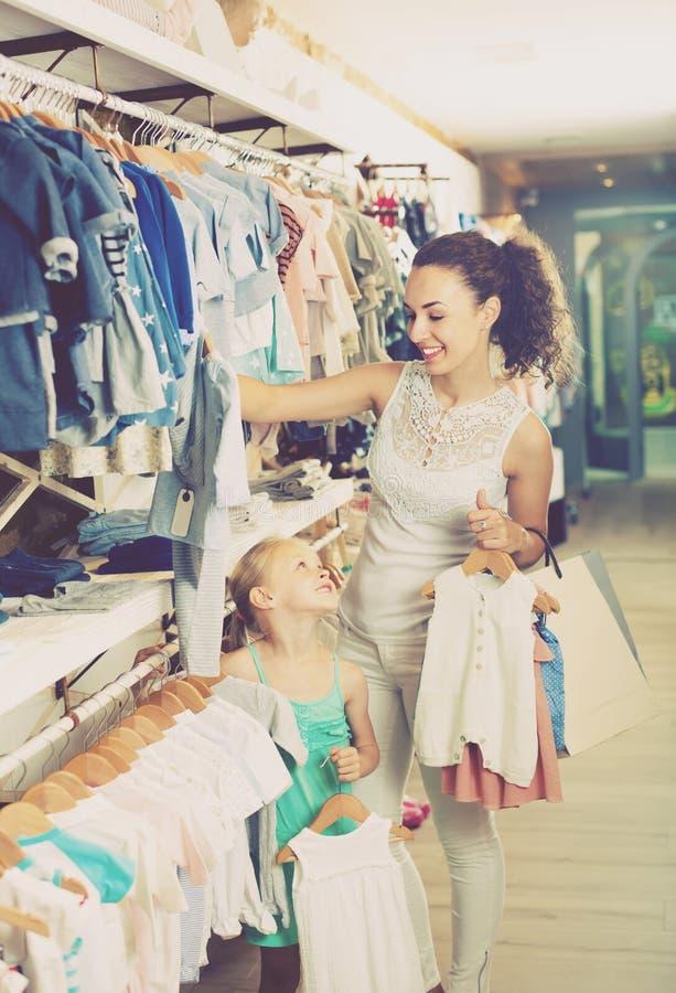 Download Jeune Mère Avec Les Pyjamas De Achat De Bébé De Fille Dans La Section D'enfants Image stock - Image du habillement, enfant: 76082167