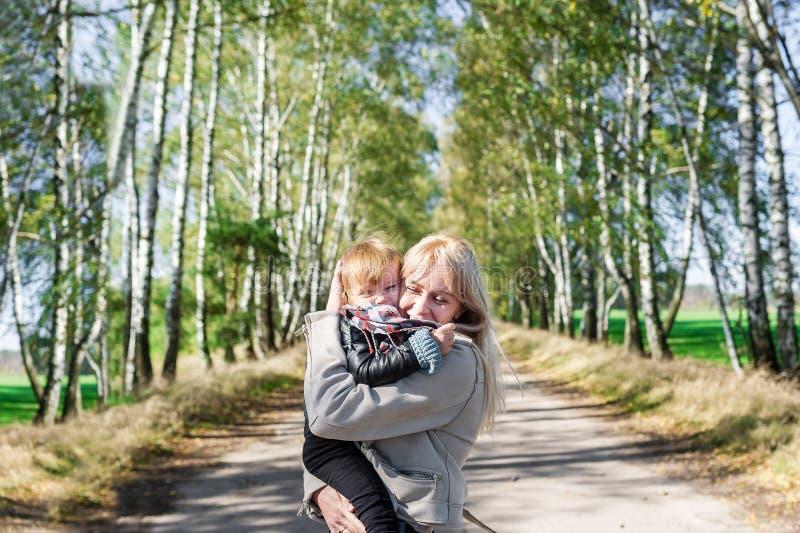 Jeune mère avec sa petite fille de bébé marchant dehors en parc d'automne images libres de droits