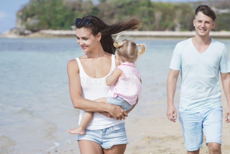 Jeune mère avec sa petite fille marchant à la plage avec photographie stock
