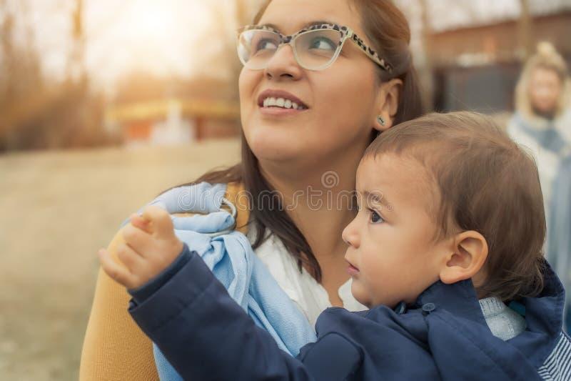 Jeune mère avec son bébé garçon dans une écharpe de transporteur de bébé photo stock