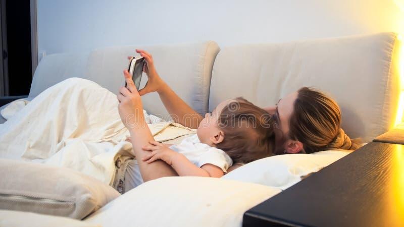 Jeune mère avec son petit garçon se situant dans le lit avec le comprimé numérique image stock