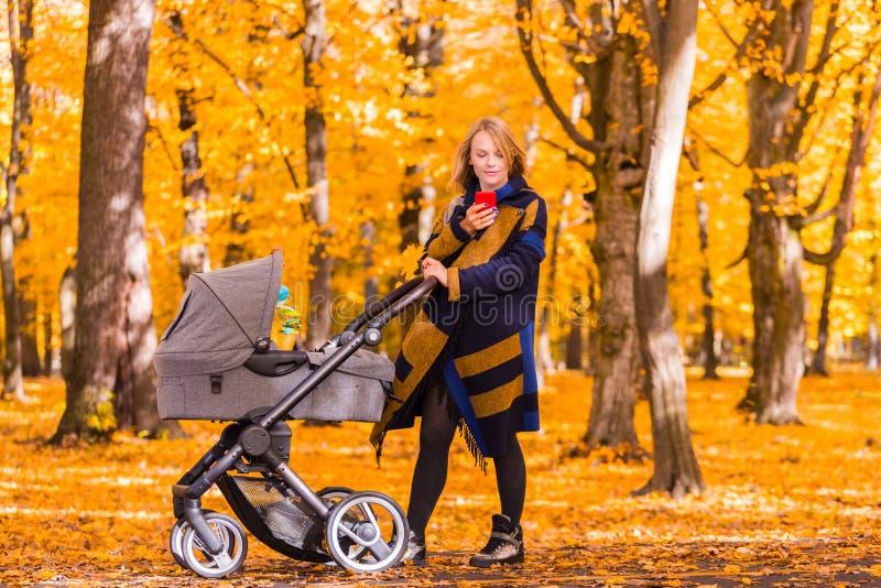 Jeune mère avec une poussette regardant un téléphone portable en parc photo stock