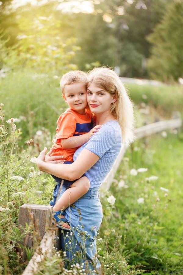 Jeune mère blonde caucasienne et petit-fils s'embrassant dans le parc extérieur pendant la journée d'été L'amour de la mère et de photos libres de droits