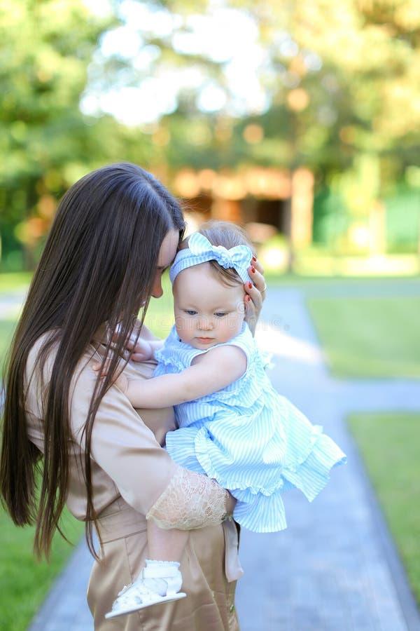 Jeune mère de brune tenant peu de bébé féminin dans le jardin photographie stock