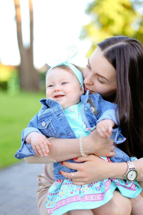 Jeune mère de brune tenant peu de veste de port de jeans de fille images stock