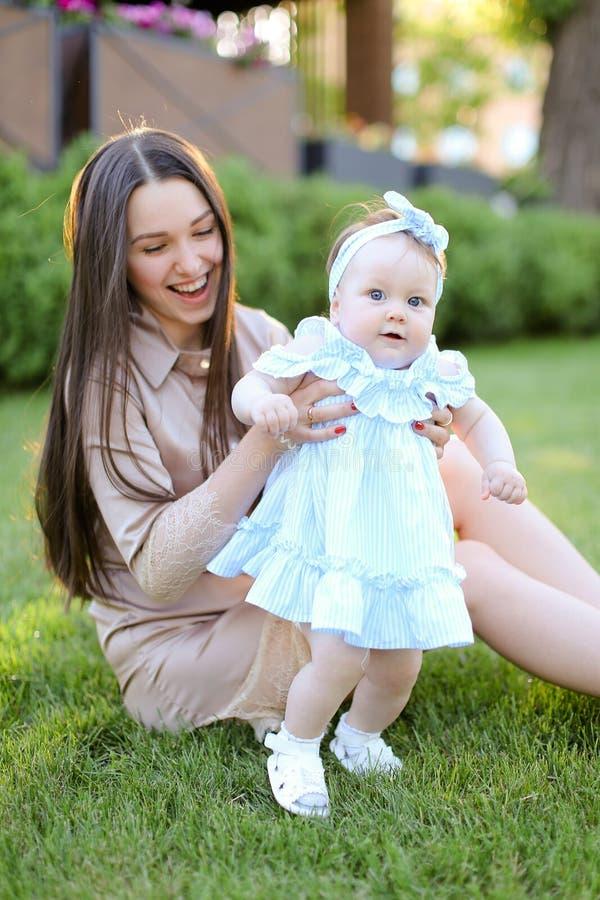 Jeune mère de sourire s'asseyant sur l'herbe avec peu de fille image libre de droits