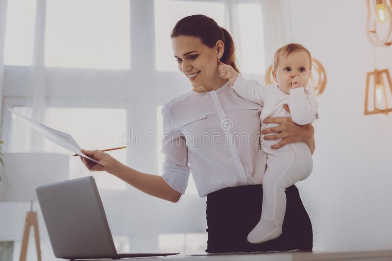 Jeune mère de travail souriant tout en soignant son petit bébé aux cheveux blonds photos stock
