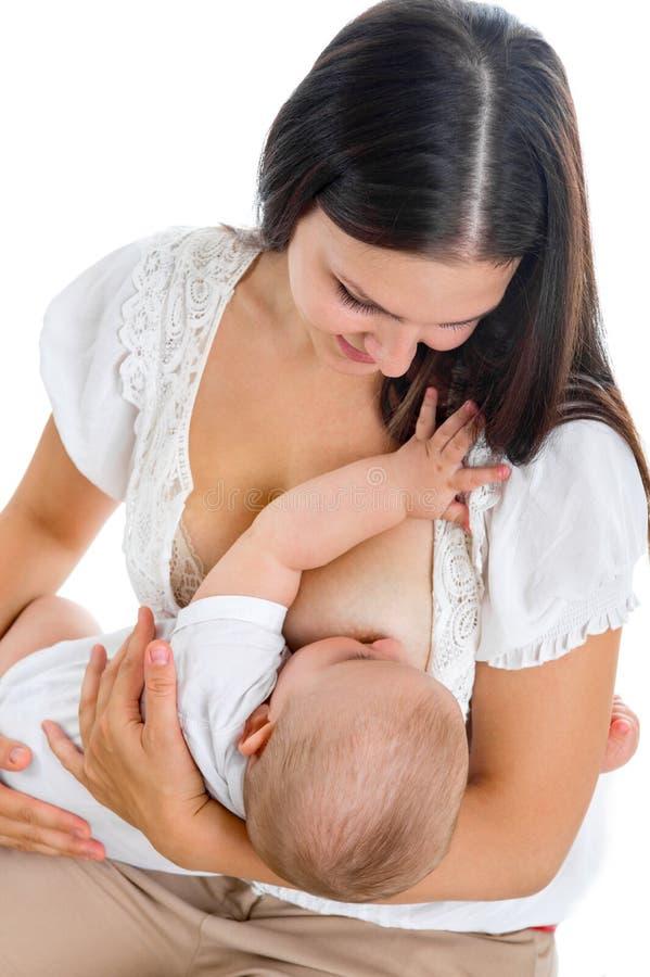 Jeune mère donnant le lait maternel à son bébé sur le fond blanc images libres de droits