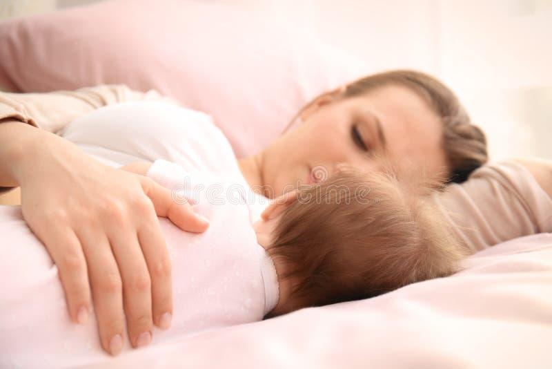 Jeune mère et bébé mignon dormant sur le lit photos stock