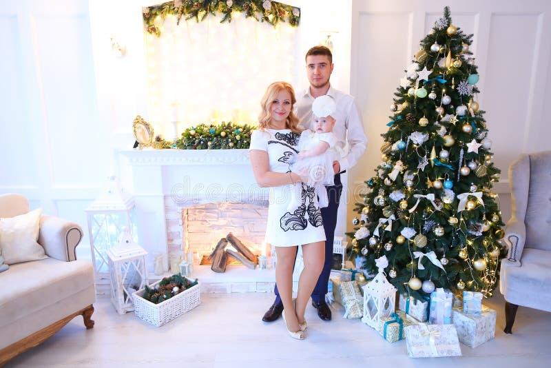 Jeune mère et père caucasiens gardant le petit bébé féminin près de l'arbre de Noël et de la cheminée décorée photographie stock