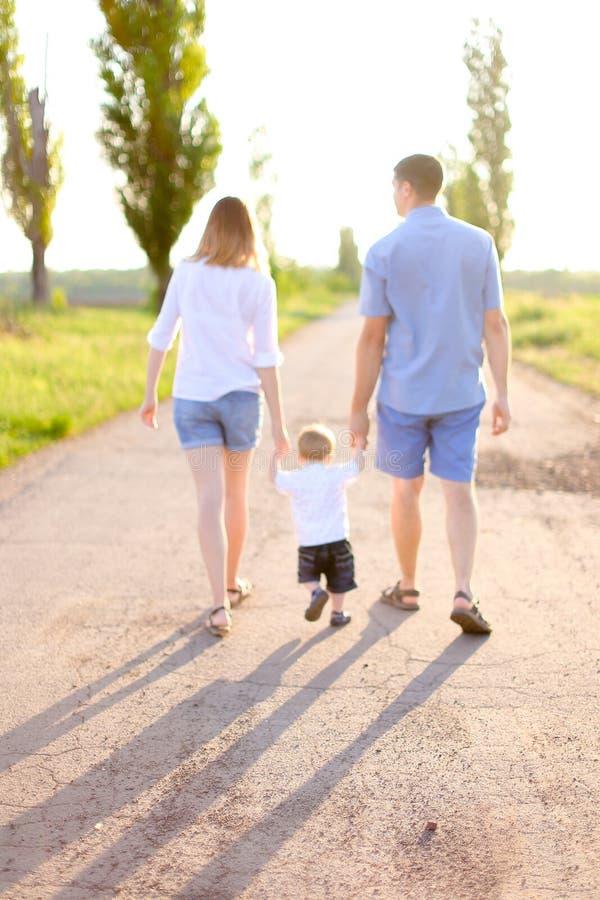Jeune mère et père marchant sur la route avec peu de bébé, temps de soleil image stock