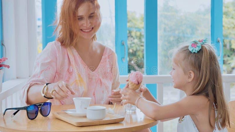 Jeune mère et sa petite fille passant le temps dans un café avec la crème glacée  photos libres de droits