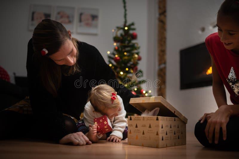 Jeune mère et ses deux filles s'asseyant sur le plancher de salon jetant un coup d'oeil à l'intérieur d'un boîte-cadeau légèremen photo stock