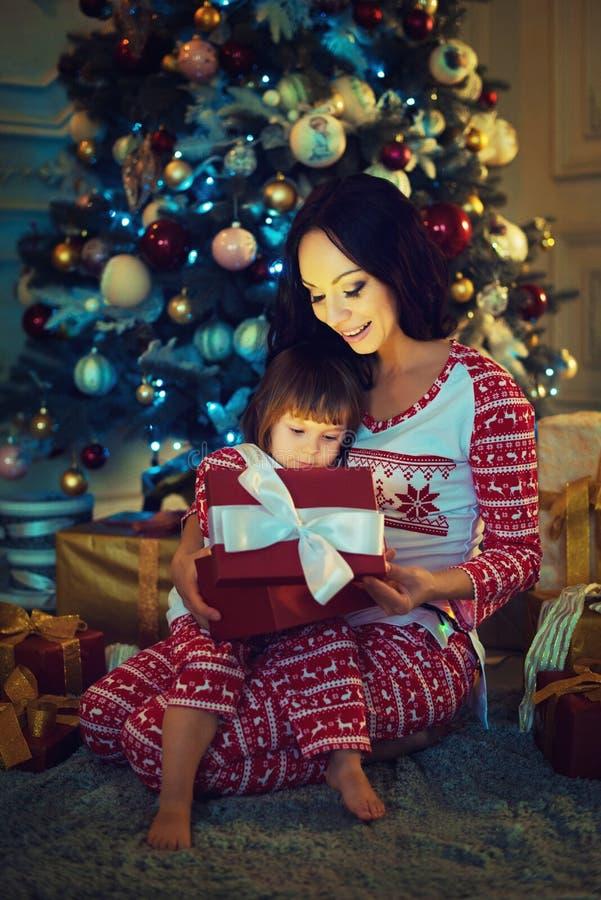 Jeune mère et ses deux petites filles ouvrant un cadeau magique de Noël par un arbre de Noël images libres de droits