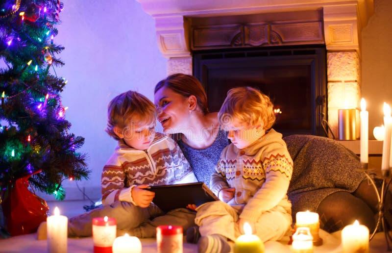 Jeune mère et ses deux petits enfants s'asseyant par une cheminée à la maison le temps de Noël Badine des garçons jouant avec le  photographie stock