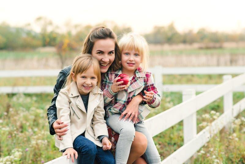 Jeune mère et ses petites filles en randonnée à la campagne Bonne famille sur la nature Relations, bonne humeur et images libres de droits