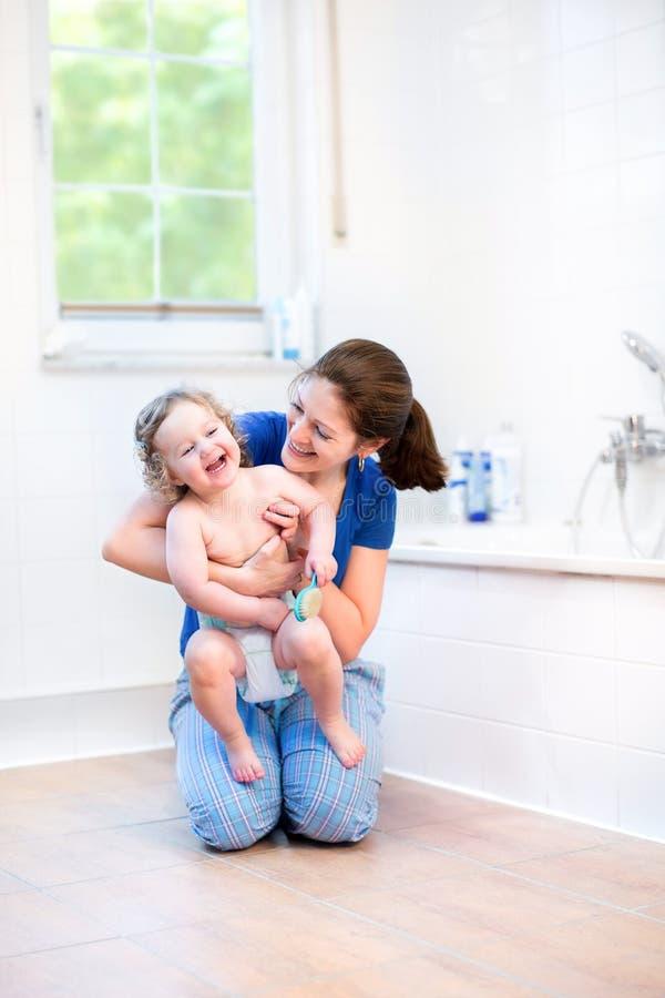 Jeune mère et son bébé heureux dans la salle de bains photos stock