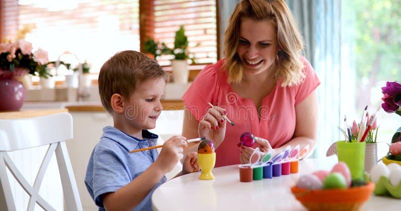 Jeune mère et son fils ayant l'amusement tandis que la peinture eggs pour Pâques image libre de droits