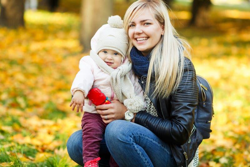Jeune mère heureuse avec la fille en parc parmi les arbres jaunes photos stock