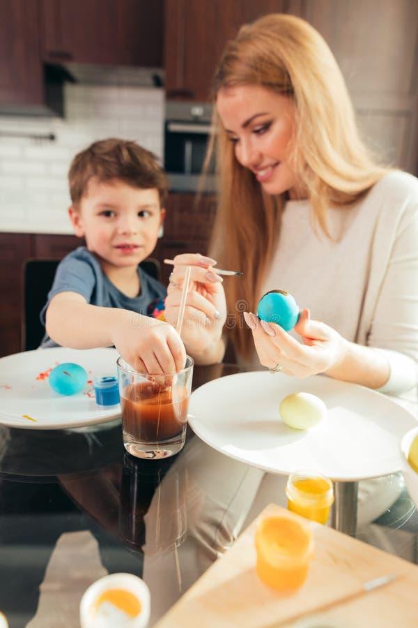 Jeune mère heureuse de Pâques et son petit fils peignant des oeufs de pâques photos stock