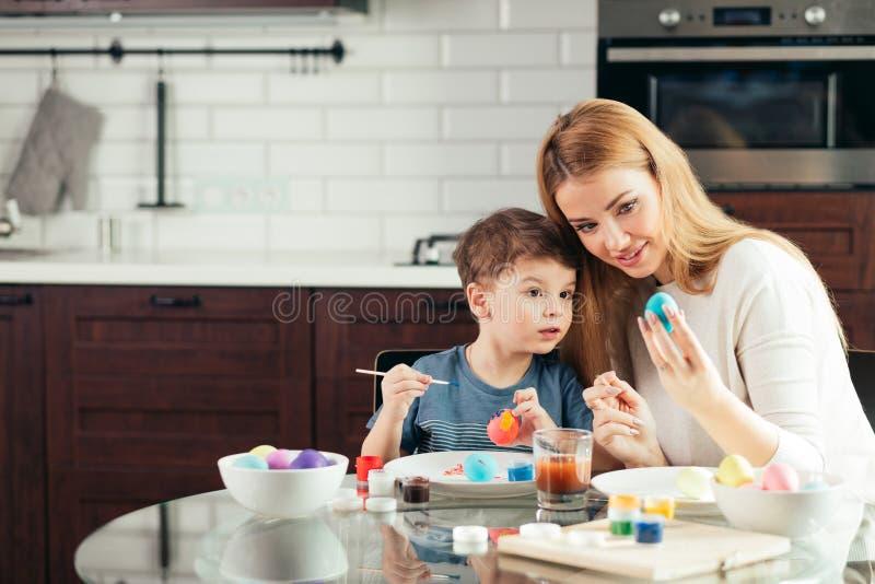 Jeune mère heureuse de Pâques et son petit fils peignant des oeufs de pâques image libre de droits