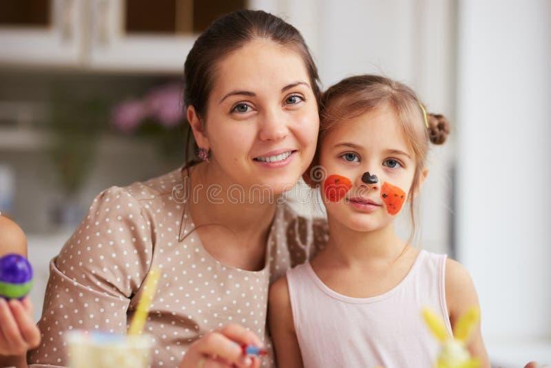 Jeune mère heureuse et sa petite fille avec le visage peint dans la cuisine légère confortable image stock