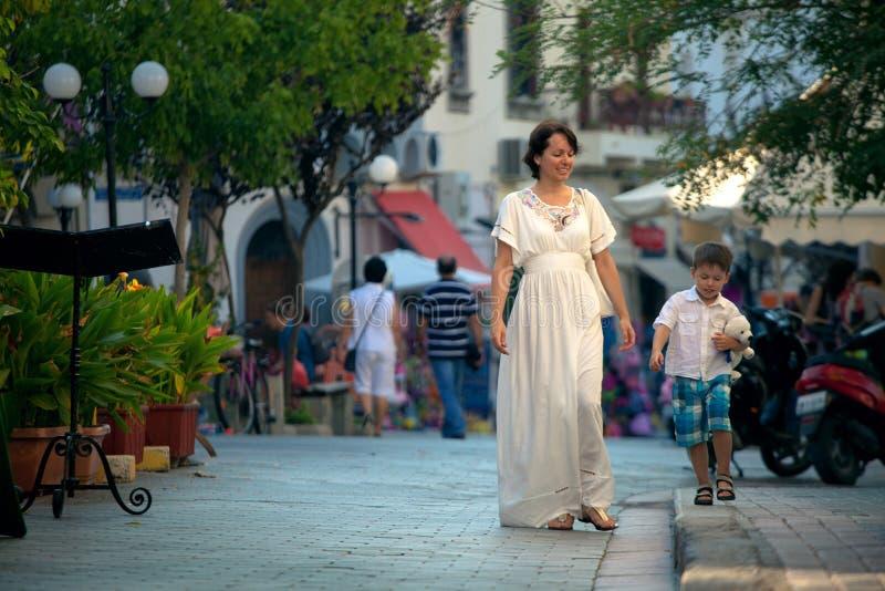 Jeune mère heureuse et son fils marchant dans la ville images stock