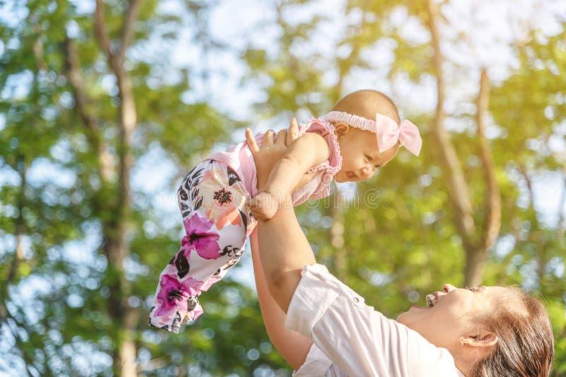 Jeune mère heureuse jouant avec de petits 5 mois de fille en parc Mère riante de moment de beau bébé la tenant dans le ciel images libres de droits