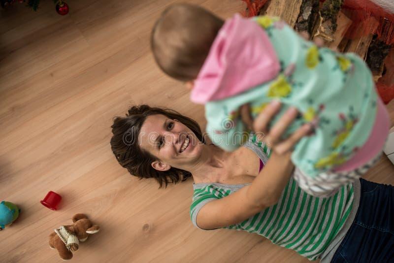 Jeune mère heureuse jouant avec la fille de bébé photo stock