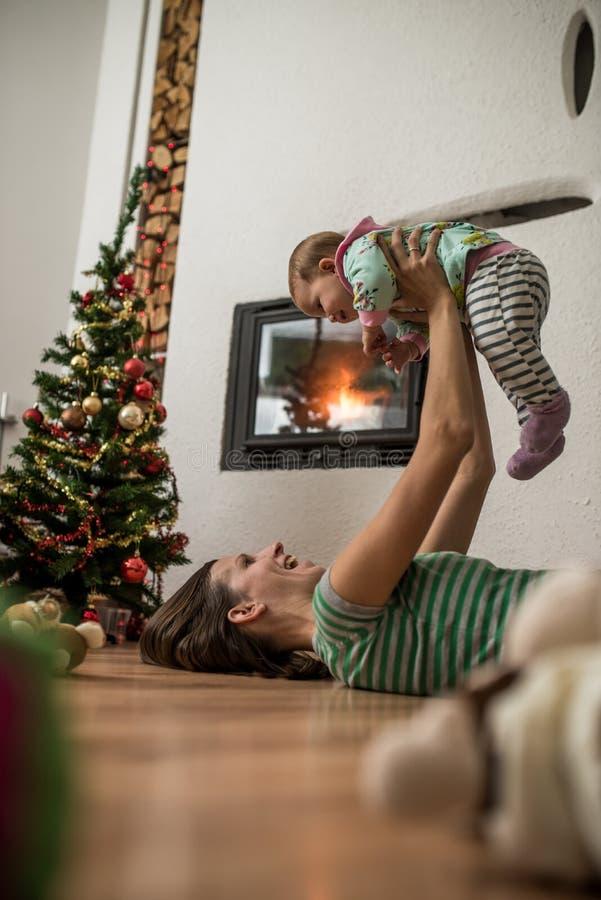 Jeune mère heureuse jouant avec sa fille de bébé photographie stock