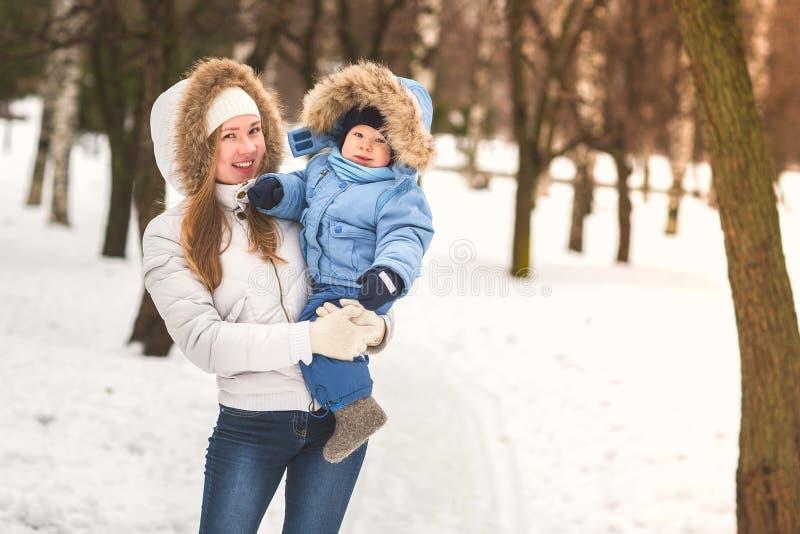 Jeune mère heureuse marchant avec son bébé en parc en hiver photographie stock