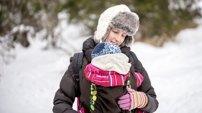 Jeune mère heureuse portant son bébé dans un transporteur photos libres de droits