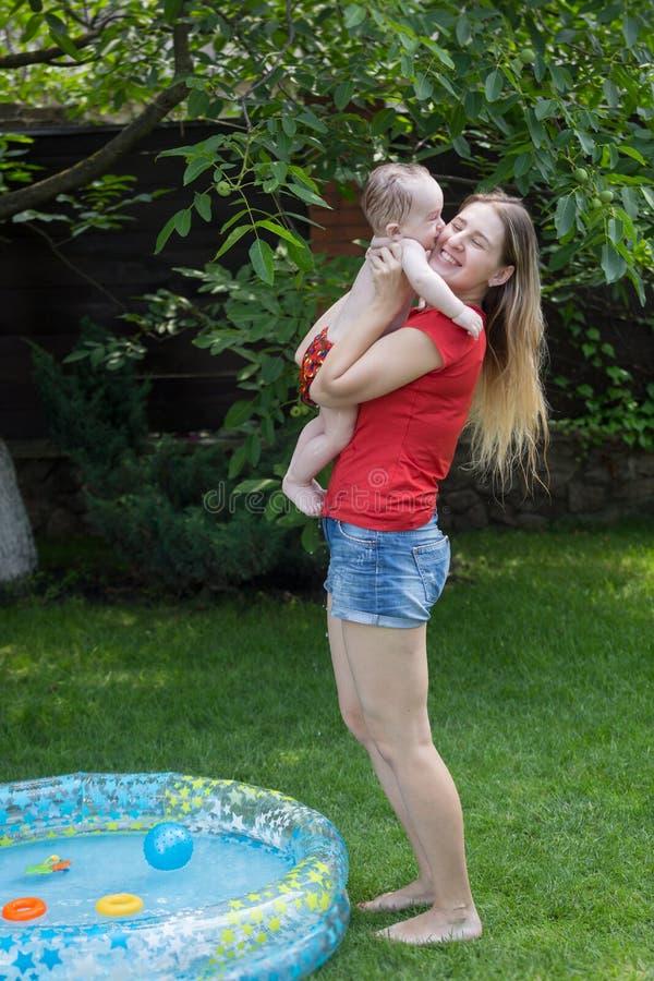 Jeune mère heureuse prenant son fils de bébé hors de la piscine gonflable image stock