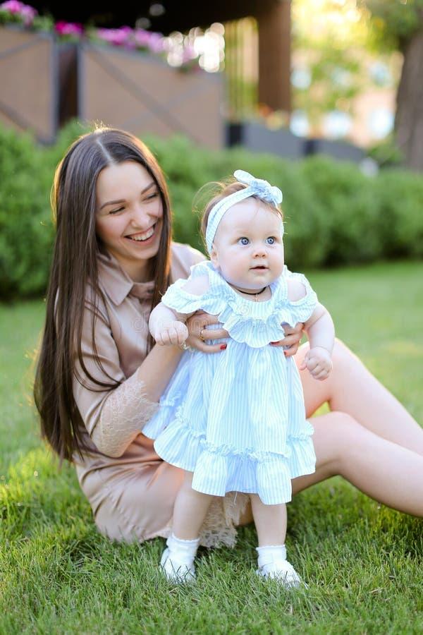 Jeune mère heureuse s'asseyant sur l'herbe avec peu de fille image libre de droits