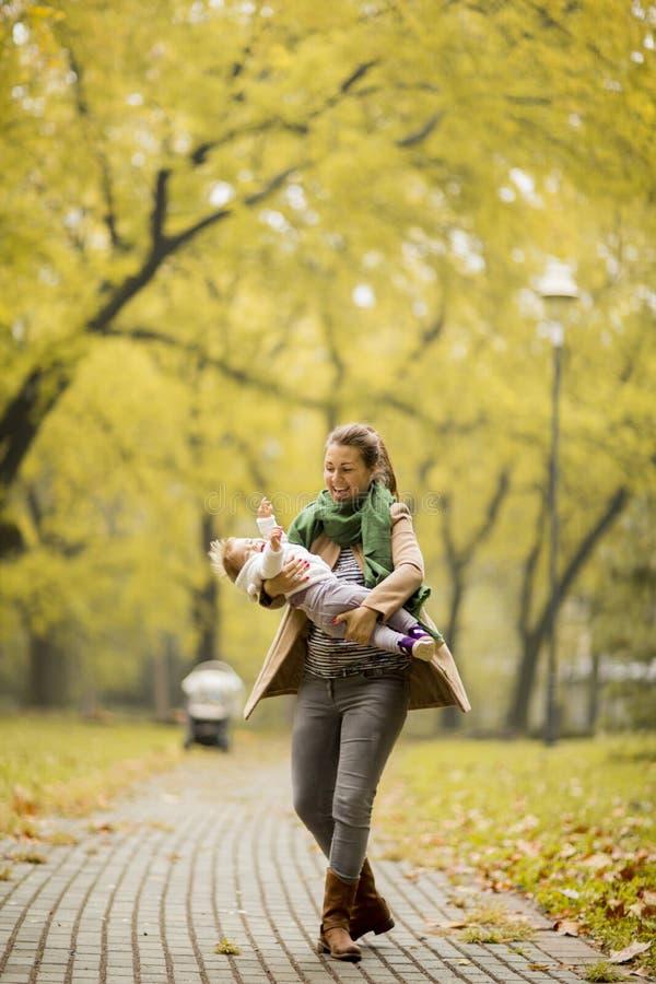 Jeune mère jouant avec le descendant en stationnement d'automne images libres de droits