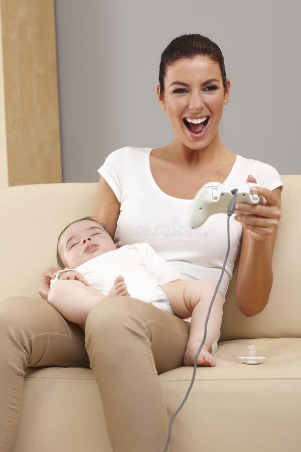 Jeune mère jouant le jeu vidéo photo libre de droits