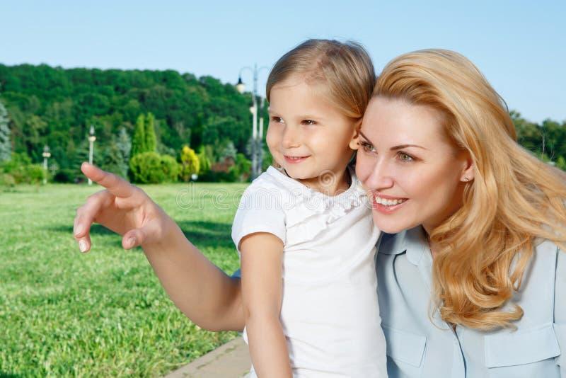 Jeune mère montrant quelque chose à sa fille images libres de droits