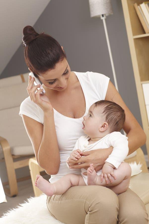 Jeune mère parlant sur l'observation mobile de bébé photographie stock libre de droits