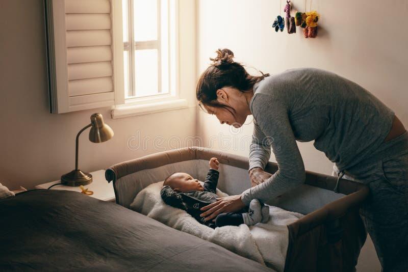 Jeune mère regardant son bébé dormant dans une huche images stock