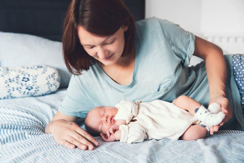 Jeune mère regardant sur son bébé nouveau-né image libre de droits