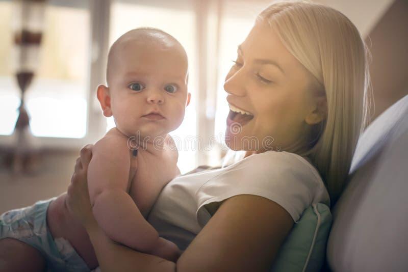 Jeune mère tenant son bébé garçon dans des bras images libres de droits