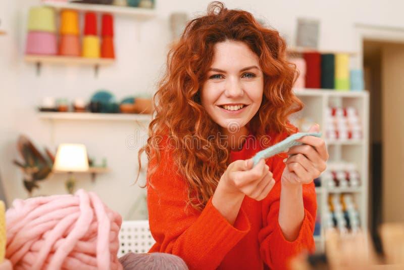 Jeune mère tricotant quelque chose pour son bébé garçon photo stock