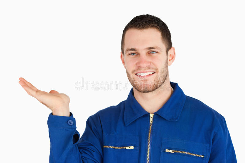 Jeune mécanicien de sourire présent quelque chose image stock