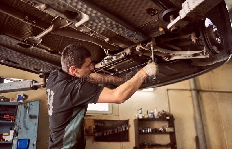 Jeune mécanicien de voiture expérimenté se tenant sous une voiture élévée pendant le processus de réparation dans un garage photographie stock libre de droits