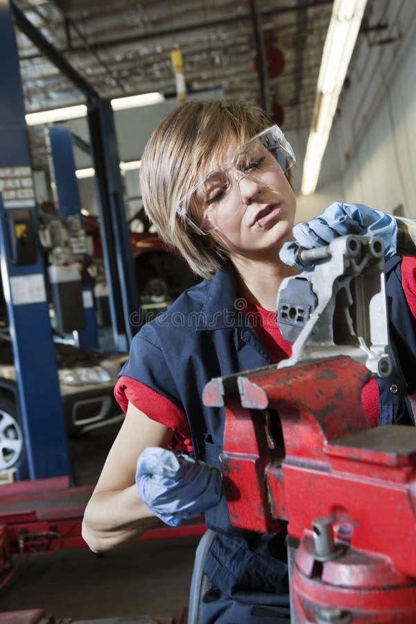 Jeune mécanicien féminin dans les vêtements de travail protecteurs travaillant à la pièce de machines dans l'atelier de réparation photo stock
