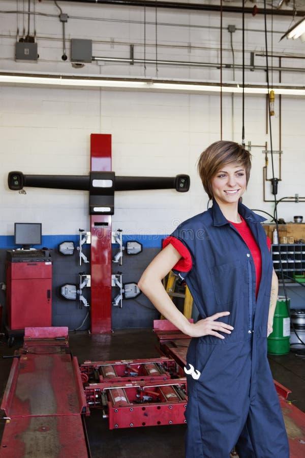 Jeune mécanicien féminin heureux avec des mains sur des hanches dans l'atelier de réparations d'automobile photographie stock libre de droits