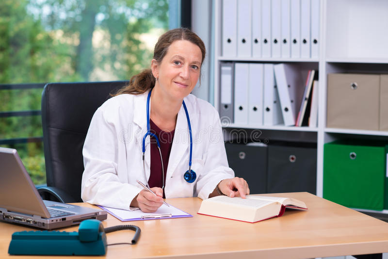 Jeune médecin de famille féminin dans son bureau photo stock