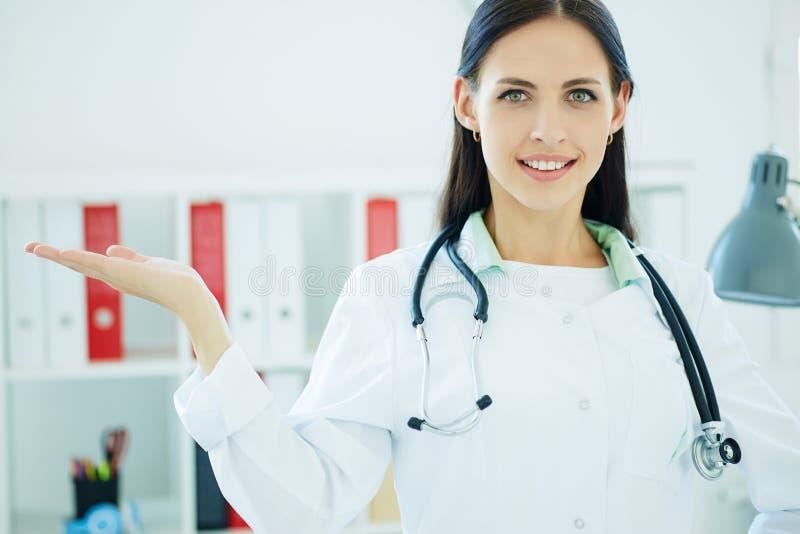 Jeune médecin féminin montrant l'espace de copie pour le produit ou le texte au-dessus de la paume Concept de publicité photo libre de droits