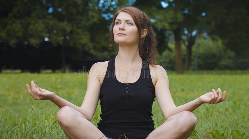 Jeune méditation de femme de forme physique en parc de ville photos libres de droits